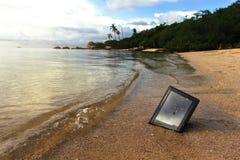 Tableta estrellada en la playa imagenes de archivo