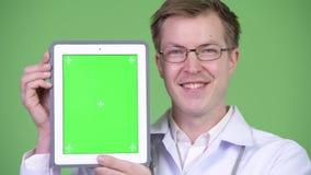 Tableta feliz de Digitaces de la pantalla del verde del doctor Showing Chroma Key del hombre almacen de video