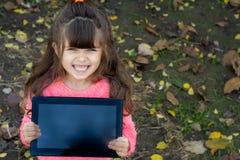Tableta feliz de la demostración del niño como si haga publicidad de ella, y colócase sobre fondo del otoño fotografía de archivo libre de regalías