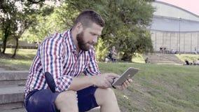 Tableta feliz de la ojeada del hombre, sentándose en las escaleras almacen de metraje de vídeo