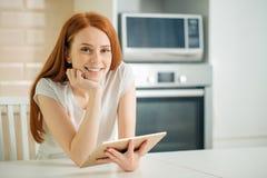 Tableta feliz de la tenencia de la mujer joven y mirada de la cámara foto de archivo libre de regalías