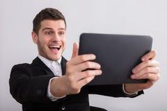 Tableta feliz de Looking At Digital del hombre de negocios imagen de archivo libre de regalías