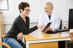Tableta feliz del doctor Communicating Over Digital del paciente y del varón imagenes de archivo