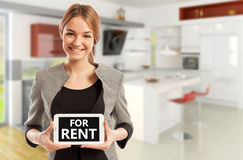 Tableta femenina de la tenencia del vendedor de las propiedades inmobiliarias con para el texto del alquiler Fotos de archivo libres de regalías