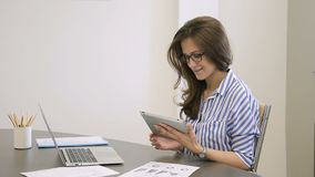 Tableta femenina de los controles del empleado en las manos que se sientan en oficina moderna