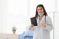 Tableta femenina joven de la tenencia del médico y un punto del finger al dispositivo imagenes de archivo