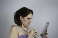 Tableta frustrada de las aplicaciones de mujer joven Imagenes de archivo