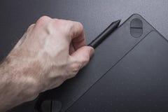 Tableta gráfica con el primer de la pluma La mano del ` s del artista con la tableta gráfica Imagen de archivo libre de regalías