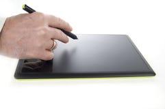 Tableta gráfica electrónica con la mano y la pluma ejecutivas Fotos de archivo libres de regalías