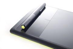 Tableta gráfica y pluma en el fondo blanco Foto de archivo libre de regalías