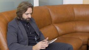 Tableta hermosa de las aplicaciones del hombre de negocios que se sienta en el sofá almacen de metraje de vídeo