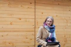 Tableta hermosa rubia de la tenencia de la mujer al aire libre fotos de archivo libres de regalías