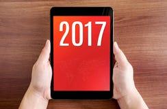 Tableta holdling de la mano con número de 2017 años en la pantalla en la etiqueta de madera Imagen de archivo libre de regalías
