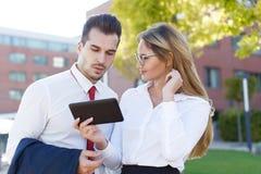 Tableta joven de la demostración de la empresaria al hombre de negocios al aire libre fotos de archivo