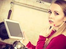 Tableta joven de la tenencia de la mujer del adolescente en cocina Imagenes de archivo
