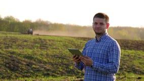 Tableta joven de la tenencia del granjero delante del tractor en campo Trabajador agrícola estacional Ecología del concepto, tran almacen de metraje de vídeo