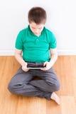 Tableta joven de la tenencia del muchacho que se sienta que se inclina en la pared Imágenes de archivo libres de regalías