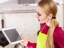 Tableta joven de la tenencia de la mujer del adolescente en cocina Fotografía de archivo libre de regalías