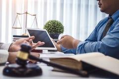 Tableta masculina de la demostración del abogado para explicar un acuerdo de contrato al cliente para la ley Concepto de la ley y foto de archivo
