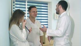 Tableta masculina de la tenencia del doctor que habla con dos otras a doctores en el pasillo del hospital almacen de metraje de vídeo