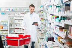 Tableta masculina de Updating Stock In Digital del farmacéutico Fotos de archivo