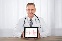 Tableta masculina del doctor Showing Heartbeat On Digital fotografía de archivo