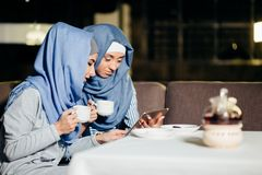 Tableta musulmán bonita del uso de la mujer en café Imagenes de archivo