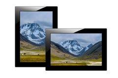 Tableta negra moderna aislada en el fondo blanco PC y pantalla de la tableta con la imagen de montañas fotos de archivo
