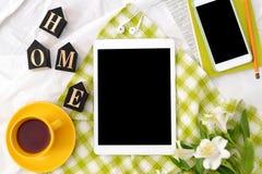 Tableta plana de la endecha, teléfono, taza amarilla de té, ordenador portátil y flores en la manta blanca con la servilleta verd Foto de archivo libre de regalías