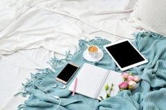 Tableta plana, teléfono, taza de café y flores de la endecha en la manta blanca con la tela escocesa de la turquesa Fotografía de archivo libre de regalías