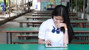 Tableta que mecanografía de la muchacha hermosa adolescente tailandesa del estudiante almacen de metraje de vídeo