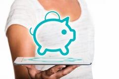 Tableta que presenta el piggybank como holograma Imagenes de archivo