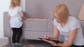 Tableta rubia atractiva joven de la ojeada de la mamá mientras que su hija encantadora que juega bloques de madera almacen de video