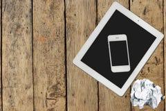 Tableta, smartphone y documento sobre la tabla de madera Fotos de archivo