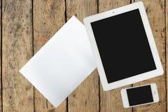 Tableta, smartphone y documento sobre la tabla de madera Imagen de archivo