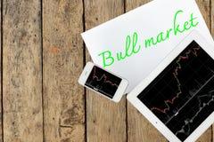 Tableta, smartphone y papel con el mercado alcista del texto en la tabla de madera Fotos de archivo libres de regalías