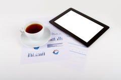 Tableta, té en cartas financieras del gráfico fotografía de archivo