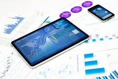 Tableta, teléfono celular y documentos financieros Imagen de archivo libre de regalías