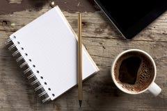 Tableta, teléfono, libreta y café en la tabla de madera Fotografía de archivo
