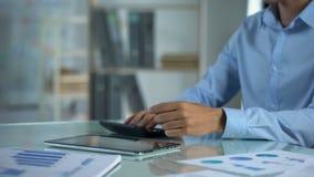 Tableta trastornada del movimiento en sentido vertical del hombre de negocios, contando la calculadora, pequeña renta de empresas almacen de video