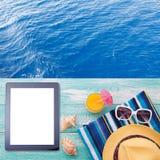 Tableta vacía en blanco en la playa Accesorios de moda del verano en piscina de madera del fondo Gafas de sol, zumo de naranja y  Imagen de archivo