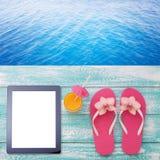 Tableta vacía en blanco en la playa Accesorios de moda del verano en piscina de madera del fondo Gafas de sol, zumo de naranja y  Fotografía de archivo
