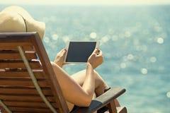 Tableta vacía en blanco en las manos de mujeres en la playa Fotos de archivo libres de regalías
