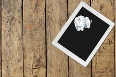 Tableta y documento sobre la tabla de madera Imagenes de archivo