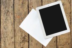 Tableta y documento sobre la tabla de madera Foto de archivo