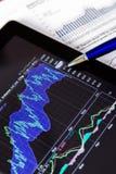 Tableta y documentos de Digitaces con los gráficos de negocio imagen de archivo