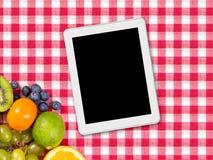 Tableta y fruta en la materia textil del mantel imagenes de archivo