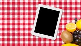 Tableta y fruta en la materia textil del mantel fotografía de archivo libre de regalías