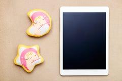Tableta y juguete digitales modernos blancos del bebé en textura de la tela imagen de archivo