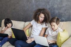 Tableta y ordenador portátil del wirh de la muchacha de la niña, del muchacho adolescente y del pelo rizado Foto de archivo